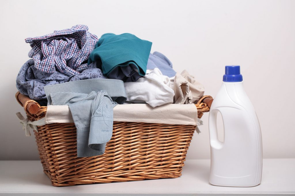 38735149 - dirty clothes in the laundry basket and a bottle of detergent